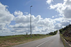 Long Straight Empty Tarmac Road with Street Lamps Royalty Free Stock Images