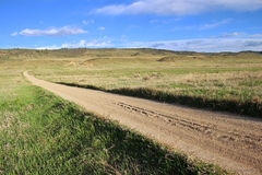 Long straight gravel road in the prairie. Stock Photos