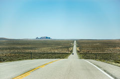 Long straight highway, blue sky, Utah. The long and straight highway among the plain in desert area of Utah with a rock mountain faraway backdrop in bright blue Stock Photo