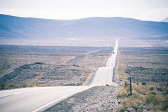 A long straight hilly road through Death Valley. This picture shows a long straight hilly road through Death Valley Arizona royalty free stock images