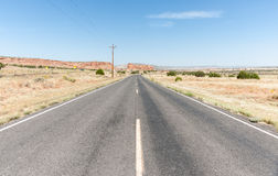 Long straight road ahead through desert of New Mexico, USA. Long straight road Route 66  ahead paralleling the current interstate highway to left through desert Royalty Free Stock Image