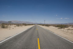 Long straight road through barren desert landscape of California. USA Royalty Free Stock Photos