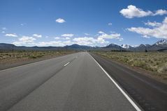Long straight road through barren prairie landscape of California Royalty Free Stock Images
