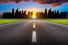 A long straight road and cityscape at sunset royalty free stock photography