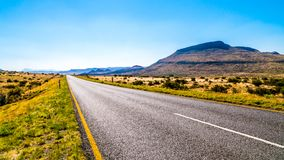 Long Straight Road through the Endless wide open landscape of the semi desert Karoo Region in Free State and Eastern Cape province. S in South Africa under blue Royalty Free Stock Image