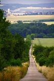 Long straight road by field in czech countryside Stock Photo