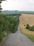 Long straight road between fields and meadows. South Moravia royalty free stock photo