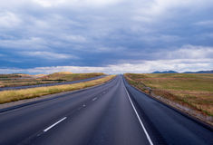 Long straight road going cloudly horizon in California Royalty Free Stock Photo