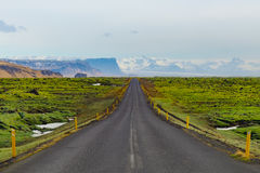Long straight road in Iceland. Long straight road crossing the famous Mossy lava field in Vik, South of Iceland Royalty Free Stock Photo
