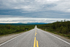 Long straight road in norway. A long, straight road running to the horizon Royalty Free Stock Photo