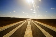 Long Straight Road and Runway Markings. Wide angle shot of long straight road with runway markings and sun in picture causing lens flare. Eyre Highway, Nullarbor Royalty Free Stock Photography