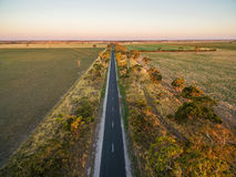 Long straight road in rural area among green fields and pastures. At sunset - aerial view Royalty Free Stock Image