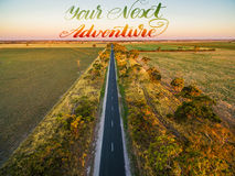 Long straight road in rural area among green fields and pastures. At sunset - aerial view with hand written text - Your Next Adventure Stock Image