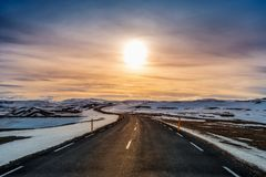 A long straight road at sunset in winter royalty free stock photo