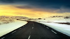 A long straight road at sunset in winter.  Stock Photos