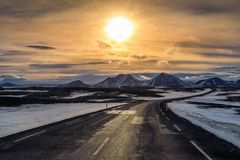 A long straight road at sunset in winter royalty free stock image