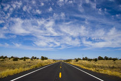 Long Straight Road under wispy clouds. Shot in Arizona on route 64 between Williams and the Grand Canyon.  Camera facing north Royalty Free Stock Photography