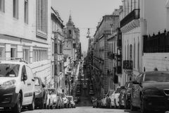 Long Straight Road in Valletta, Malta. A Long Straight Road in Valletta, Malta in black and white with a huge line of cars parked along the road Royalty Free Stock Photography