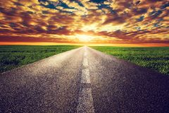 Long straight road, way towards sunset sun. Long straight road, way towards sun. Sunset sky, travel, transport, destination concepts Royalty Free Stock Photography