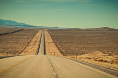Long Straight Road in Wyoming USA. Long straight strech of US highway 287 through ranch country in central Wyoming, USA. Retro instagram look Royalty Free Stock Photos