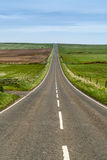 Long straight tarmac road disappearing over far horizon Stock Photo