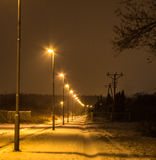 Long street with a number of lamps burning at night, winter. Background. Royalty Free Stock Photography