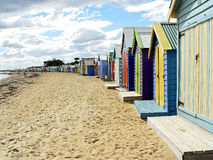 A long stretch of beachhouses. A variety of wooden beach houses stretching along Brighton Beach in Melbourne, Australia and disappearing into the distance stock images