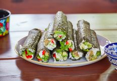 Uncut sushi rolls lying on plate. Long sushi rolls with rice, nori and vegetables lying on ceramic plate standing on wooden table with kitchenware with Royalty Free Stock Images