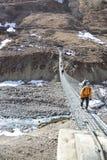 Long suspension foot bridge over deep valley Royalty Free Stock Photos