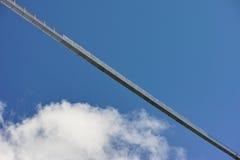 Long suspension footbridge in blue sky with cloud Stock Photo