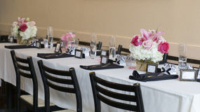 Long table with white table cloth decorated for wedding. White table cloth on the table with decor for wedding. on the table on each side are black napkins Stock Photos