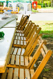 Long tables in garden row of wooden chairs. Preparation for outdoor summer picnic or public fest. Green grass, sunlight Stock Image