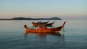 Long tail boat anchored in the sea by the dawn with the blue sky and the island in the background. Anchored Long Tail Boats in the open sea near the Koh Lipe Royalty Free Stock Photography
