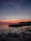 Long tail boat anchored in the shore by the dawn with the beautiful sky and the moon. Rocky shore with the sand at the dawn. Thai Long Tail Boats anchored under Stock Image