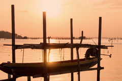 Long tail boat at beautiful sunset orange sky reflect with water lake at traditional folk fishing village in south Thailand Royalty Free Stock Photography