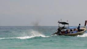 Long-tail boat with black engine smoke on Phi Phi Island, Rantee Beach 2 stock footage