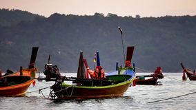 Long tail boat converted in the andaman sea with golden light of the Sun before sunset and  boat background. Group of  long tail boat converted to boat stock video footage