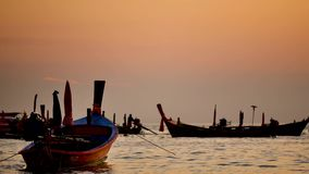 Long tail boat converted in the andaman sea with golden light of the Sun before sunset and  boat background. Group of long tail boat floating in the andaman sea stock video footage