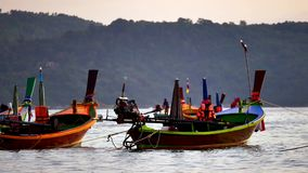 Long tail boat converted in the andaman sea with golden light of the Sun before sunset and  boat background. Group of long tail boat floating in the andaman sea stock footage