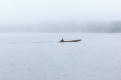 Long tail boat with a fisherman inside on river with foggy background. Stock Photo