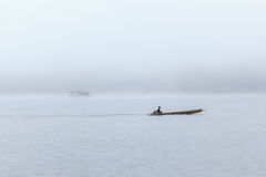 Long tail boat with a fisherman inside on river with foggy background. Royalty Free Stock Photo