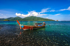 Long tail boat floating on beautiful pebble beach Stock Images