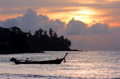 Long tail boat with orange sky stock images