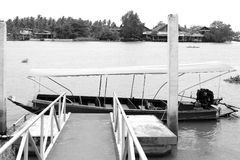 Long tail boat parking at pier rim the big river. (Black and white scene Royalty Free Stock Images