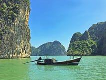 Long Tail Boat, Phang Nga Bay, Thailand. A traditional Thai vessel is anchored near the limestone karsts of Phang Nga Bay Royalty Free Stock Photo