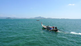 Long tail boat with the sailor on the open sea in Thailand near the Koh Muk Island Stock Photography