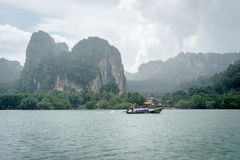 Long tail boat in sea under high mountain and cloudy sky stock images