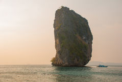 Long tail boat on tropical beach with limestone rock. Sunset, island Taming. Krabi, Thailand. Stock Photo