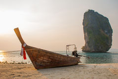 Long tail boat on tropical beach with limestone rock. Sunset, island Taming. Krabi, Thailand. Royalty Free Stock Photos