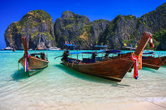 Long tail boat on white sand beach with crystal clear sea royalty free stock image